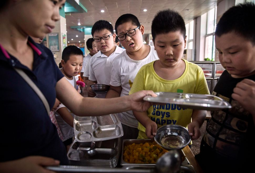 Overweight Chinese students are served a nutrition balanced lunch during a break from training at a camp held for overweight