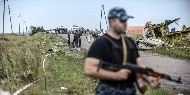 Armed pro-Russian separatists stand guard in front of the crash site of Malaysia Airlines Flight MH17, near the village of Gr