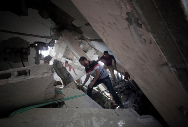 Palestinians search for survivors under the rubble of a house was destroyed by an Israeli missile strike, in Gaza City, Monda