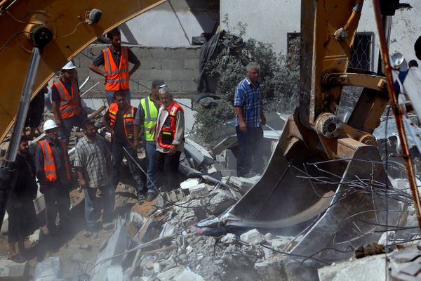 Palestinians watch rescuers searching for bodies and survivors under the rubble of an apartment building, destroyed by an Isr