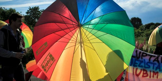 A girl casts a shadow on a rainbow colored umbrella next to a banner that