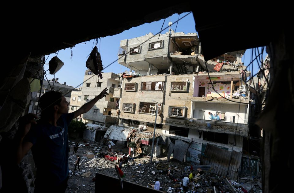 Palestinians inspect the rubble of a house after it was hit by an Israeli missile strike in Gaza City, Thursday, July 10, 201