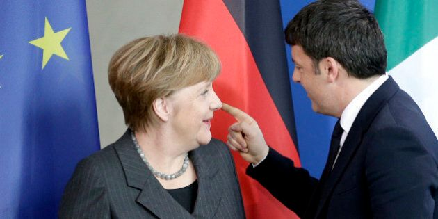 German Chancellor Angela Merkel, left, and Prime Minister of Italy Matteo Renzi, right, talk after a...