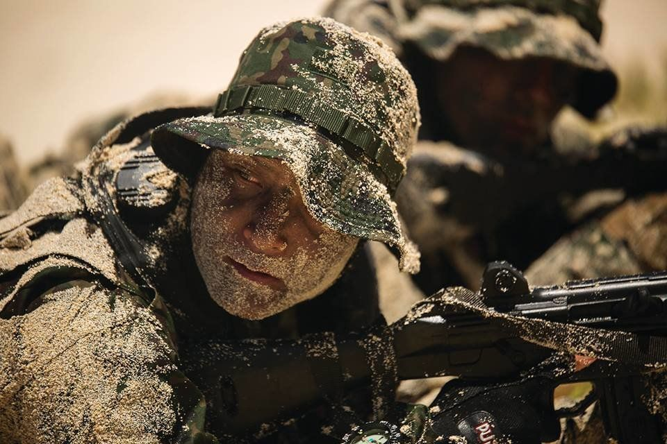 A soldier with Japan Ground Self-Defense Force (JGSDF) waits for his squad leader to give the signal to advance their positio