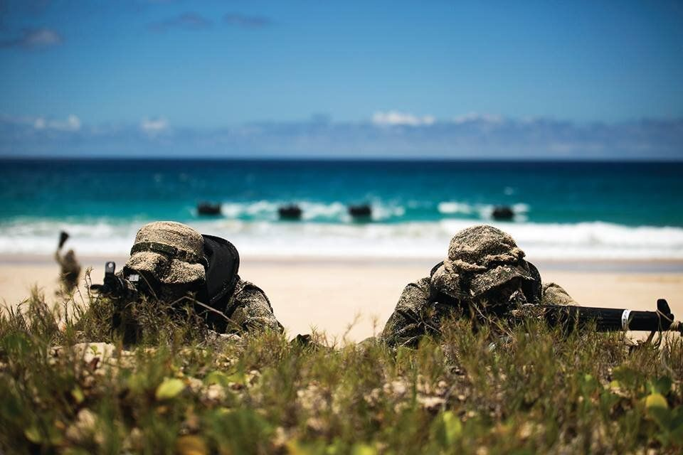 Two soldiers with the Japan Ground Self-Defense Force (JGSDF) provide security while the rest of their team moves to shore du