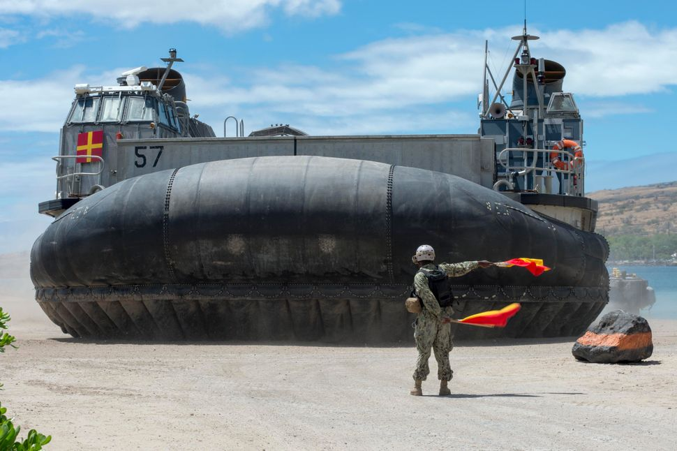 Seaman Darius Thigpen, from Chicago, directs departing Landing Craft Air Cushion (LCAC), assigned to Assault Craft Unit (ACU)