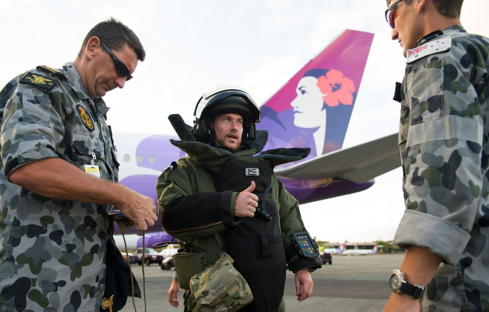 Leading Seaman Ben Beck of Australian Clearance Diving Team 1 positively confirms a radio check during a bomb-onboard plane t