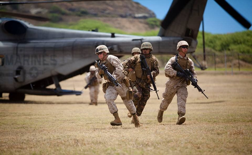 U.S. Marines, assigned to 1st Battalion, 12th Marine Regiment, and Tongan Marines, exit the back of a CH-53E Super Stallion d