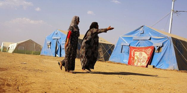 KHAZAIR, IRAQ - JUNE 28:  Iraqi women walk inside of  a displacement camp for those caught-up in the fighting in and around t