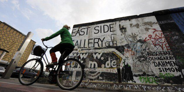 A woman cycles past a portion of the Berlin Wall on October 16, 2008 at the East Side Gallery in Berlin. The East Side Galler