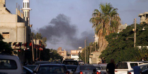Smoke billows during clashes between security forces and armed groups near a Libyan army special forces barracks, on July 23,