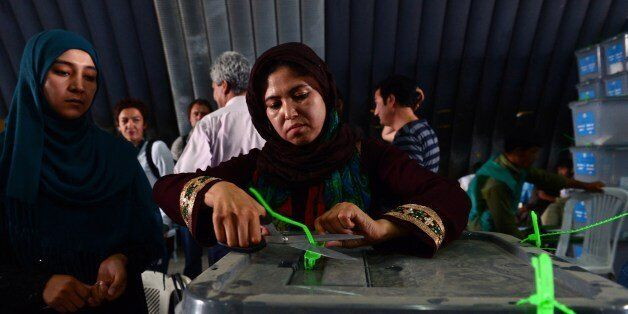 An Afghan election commission worker cuts open the seals to a box containing ballot papers for an audit of the presidential r