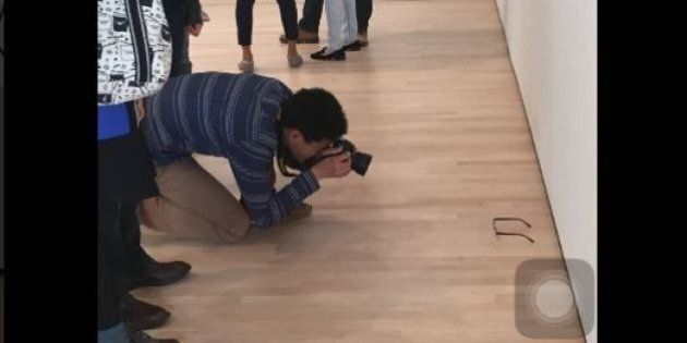 Mette gli occhiali sul pavimento in una galleria d'arte. I visitatori li scambiano per un pezzo