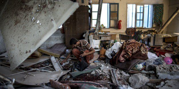 A Palestinian scout collects human remains from a classroom inside a UN school in the Jabalia refugee camp after the area was