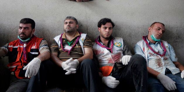 Palestinian medics take a break after carrying wounded people injured from an Israeli strike in Shijaiyah neighborhood, into