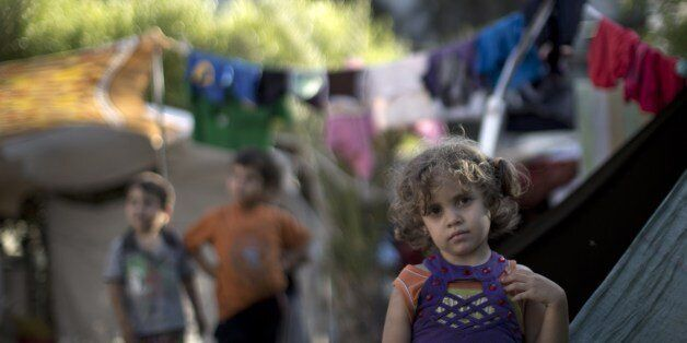 A displaced Palestinian girl stands next to a makeshift tent at the al-Shifa hospital in Gaza City where many Palestinians ha