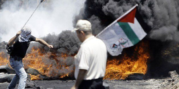 A Palestinian protester (L) hurls rocks at Israeli security forces as man walks past with a Palestinian flag during clashes f