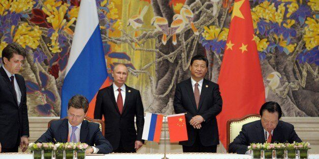 China's President Xi Jinping (back R) and Russia's President Vladimir Putin (back L) attend an agreement signing ceremony in