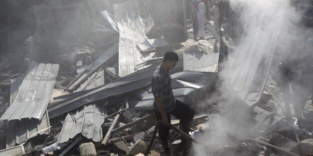 Palestinians inspect the wreckage of a building following an Israeli strike, in Rafah, in the southern Gaza Strip on August 2