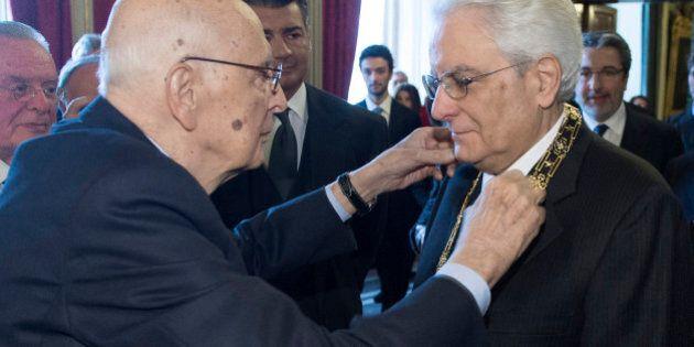 Italy's new President Sergio Mattarella (R) receives a decoration from his predecessor Sergio Napolitano...