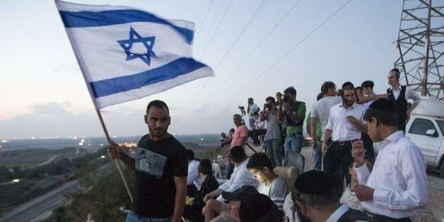 Israelis, mostly residents of the southern Israeli city of Sderot, stand with an Israeli flag on a hill overlooking the Gaza