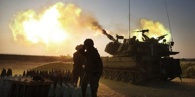 Israeli soldiers of the 155mm artillery cannons unit fire towards the Gaza Strip from their position near Israel's border wit