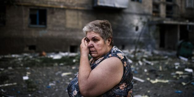 A woman reacts after shelling in the town of Yasynuvata near the rebel stronghold of Donetsk on August 12, 2014. Shelling on