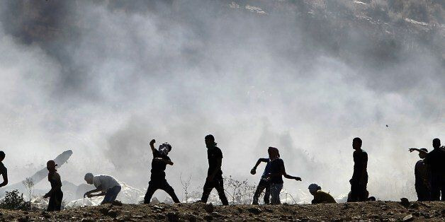 Palestinian protesters clash with Israeli security forces (unseen) following a demonstration in support of Gaza after Friday