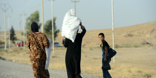 MOSUL, IRAQ - AUGUST 16: Iraqis flee their home as attacks of army groups led by Islamic State (IS), formerly known as ISIL,