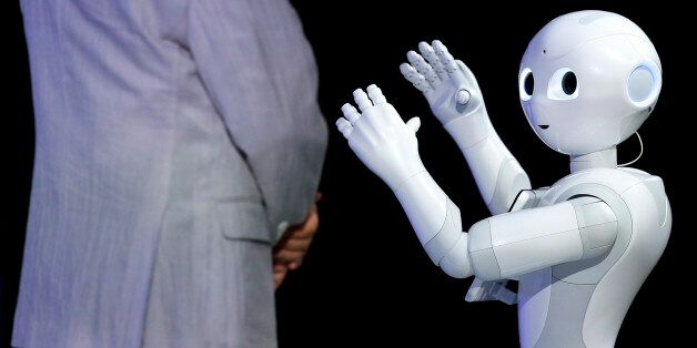Humanoid robot Pepper, developed by SoftBank Corp.'s Aldebaran Robotics unit, performs next to Masayoshi Son, chairman and ch