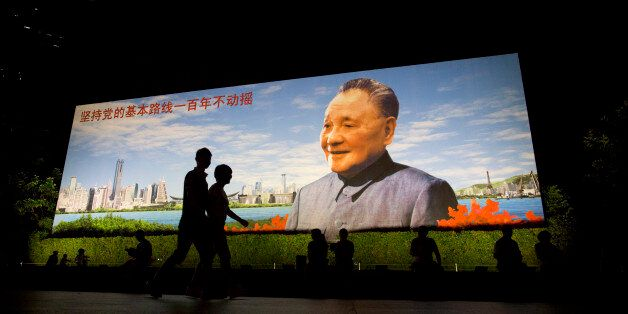 People walk past a portrait of China's former leader Deng Xiaoping that reads 'Persist with the Communist Partys fundamental