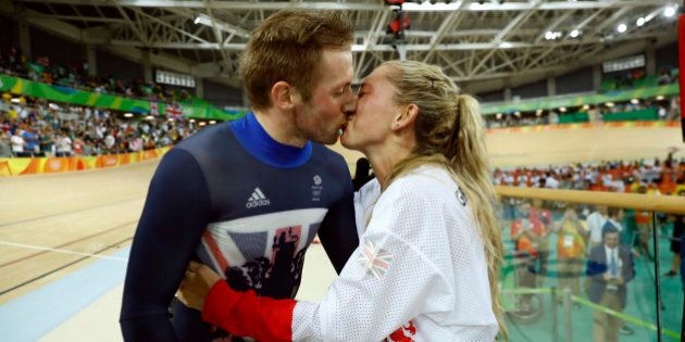 Laura Trott, right, kisses her fiance Jason Kenny, left, both of Britain, after he won the men's keirin...