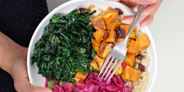 Close cropped overhead view of woman sitting cross legged on floor with bowl of healthy vegan food. Quinoa,...