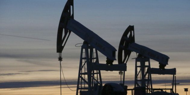 Pump jacks are seen at the Lukoil-owned Imilorskoye oil field, as the sun sets, outside the west Siberian...