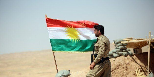 A peshmerga fighter stands next to a Kurdish flag as he guards a position near the strategic Jalawla area, in Diyala province