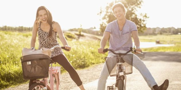 Portrait of happy young couple with legs apart cycling on country