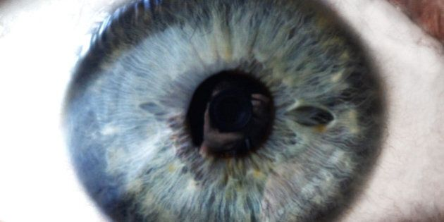Close up of open human eye with photographer