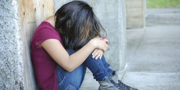 Sad, distraught tween girl outside of a concrete