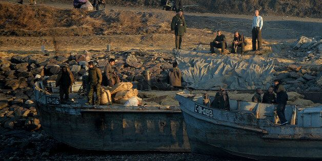 North Korean workers and soldiers sit on the banks of the Yalu River at the town of Sinuiju across from the Chinese border to