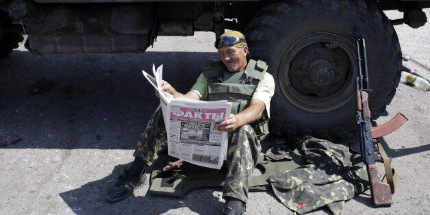 A Ukrainian soldier reads a newspaper at a checkpoint in the eastern city of Debaltseve on August 6, 2014. Russian President