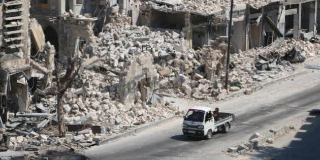 Men ride on a pick-up truck past damaged buildings in the rebel-held Bab al-Hadid neighbourhood of Aleppo,...