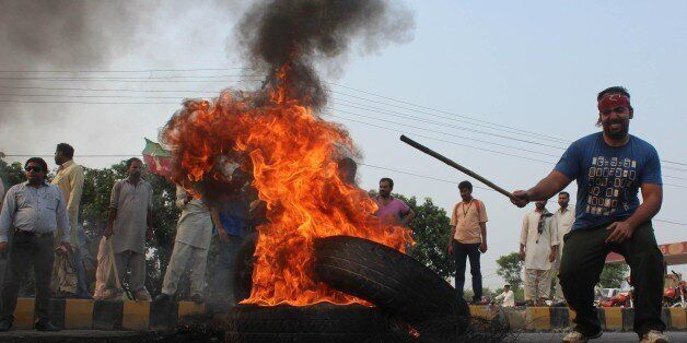 LAHORE, PAKISTAN - AUGUST 31: A supporter of the Pakistan Tehreek-e-Insaf (PTI) political party burns a tyre as they block th