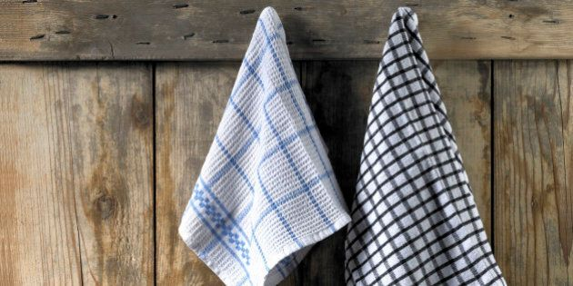 Two dishcloths hanging from an old wooden door. The dishcloths are black and white and blue and white...