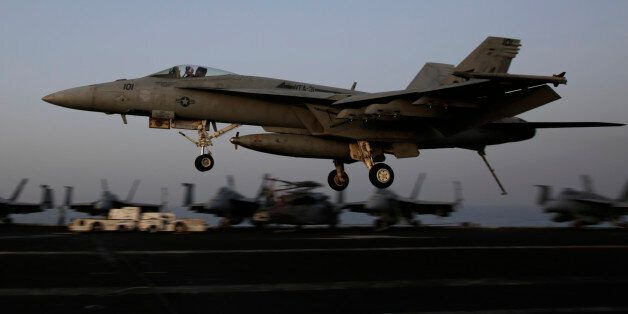 An F/A-18C Hornet coming from Iraq lands on the flight deck of the U.S. Navy aircraft carrier USS George H.W. Bush, Sunday, A