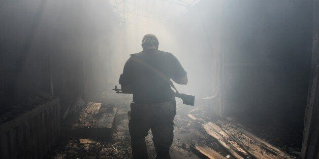 A Pro-Russian rebel walks in a passage at the local market damaged by shelling in Petrovskiy district in the town of Donetsk,