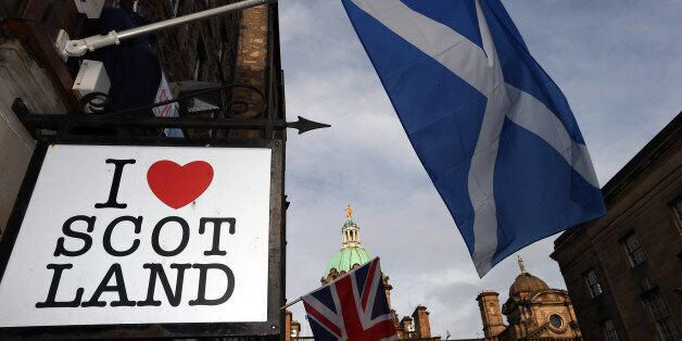 A Scottish flag and a Union flag fly outside a Scottish memorabilia shop in Edinburgh, Scotland,  Thursday, Feb. 13, 2014. Sc