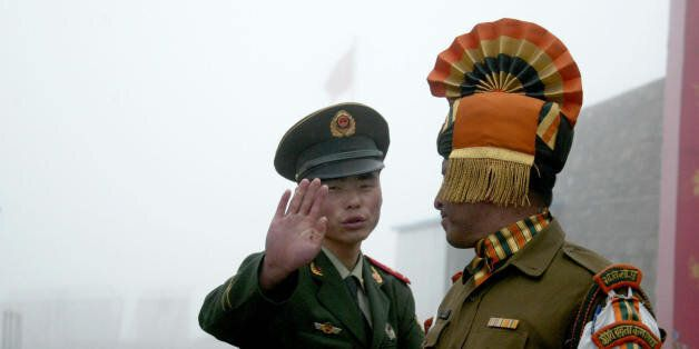 In this photograph taken on July 10, 2008, A Chinese soldier gestures as he stands near an Indian soldier on the Chinese side