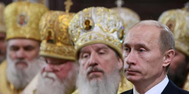 Russian Premier Vladimir Putin (R) attends the enthronement ceremony of Russian Orthodox Patriarch of Moscow and All Russia K