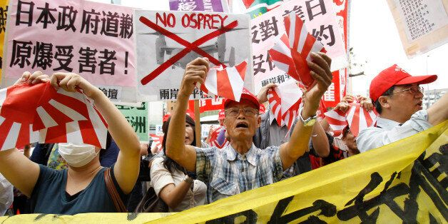 Anti-Japan protesters tear Japanese military flags during a demonstration over what they say is a growing Japanese aggression