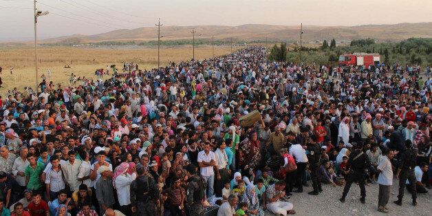 In this photo provided by UNHCR officials and taken on Thursday, Aug. 15, 2013. Syrian refugees cross the border toward Iraq
